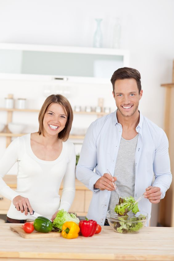young couple cooking in the kitchen preparing a meal using farm fresh ingredients for a salad